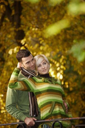 Young love couple hugging outdoor in park at autumn, smiling. photo