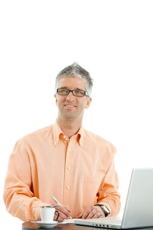undoubting: Casual businessman wearing orange shirt and jeans, standing at coffee table, using laptop computer, writing notes. Isolated on white.