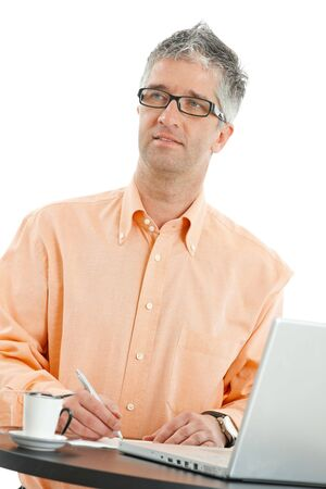Casual businessman wearing orange shirt and jeans, standing at coffee table, using laptop computer, writing notes. Isolated on white. photo