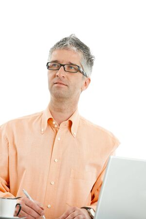 Casual businessman wearing orange shirt and jeans, thinking abouth something and writing notes. Isolated on white. photo