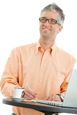 Casual businessman wearing orange shirt and jeans, writing notes at coffee table. Isolated on white. photo