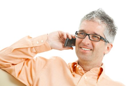 Casual man wearing jeans and orange shirt talking on mobile phone. Isolated on white. photo