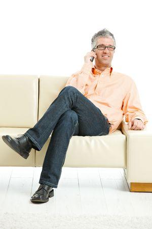 hombre sentado: El hombre informal con pantalones vaqueros y camisa naranja sentado en el sof�, hablando por tel�fono m�vil. Aislado en blanco.