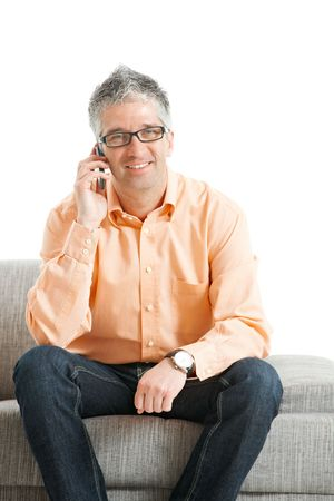 Casual man wearing jeans and orange shirt sitting on couch, talking on mobile phone. Isolated on white. photo