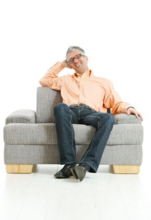 Mid-adult man wearing jeans and orange shirt sitting on couch, talking on mobile phone. Isolated on white. photo