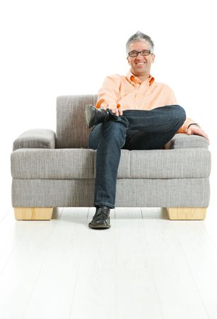 Happy man wearing jeans and orange shirt sitting on couch, talking on mobile phone. Isolated on white. photo