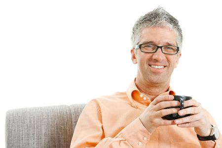 Relaxed man sitting on couch, drinking coffee, smiling. Isolated on white. photo