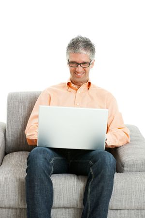 Mid-adult man wearing jeans and orange shirt sitting on couch, using laptop computer. Isolated on white. photo