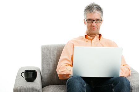 telework: Mid-adult man wearing jeans and orange shirt sitting on couch, using laptop computer. Isolated on white.