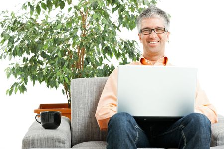 Happy man wearing jeans and orange shirt sitting on couch, browsing internet on laptop computer. Isolated on white. photo
