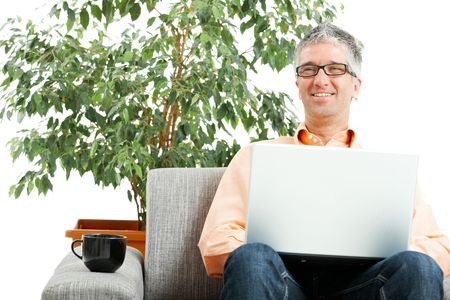 Casual man wearing jeans, orange shirt and glasses using laptop computer at home, sitting on couch. Green potted plant in the background. photo