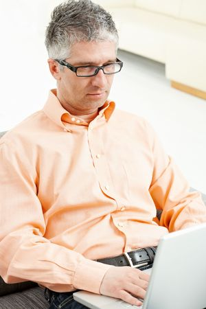 Casual man wearing jeans and orange shirt sitting on couch, working with laptop computer. photo