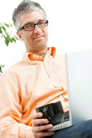 Mid-adult man sitting on couch, drinking coffee, browsing internet on laptop computer. Isolated on white. photo