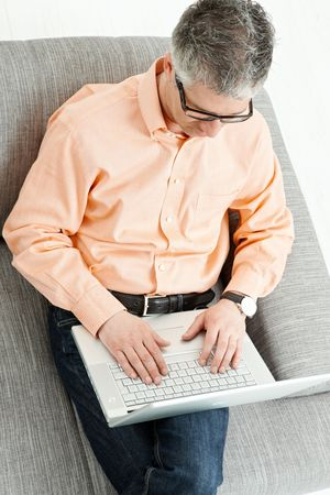 Casual man wearing jeans and orange shirt sitting on couch, working with laptop computer. Overhead shot. photo