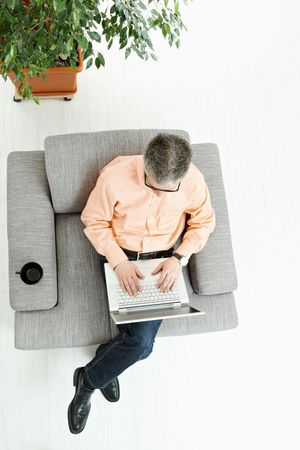 Grey haired man wearing jeans and orange shirt sitting on couch, working on laptop computer. High angle view. photo