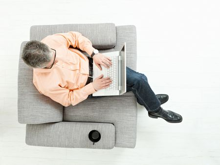 Grey haired man wearing jeans and orange shirt sitting on couch, working on laptop computer. Overhead shot. photo