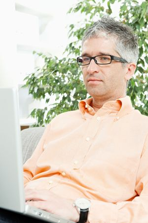 Mid-adult man wearing jeans and orange shirt sitting on couch, working with laptop computer.  photo