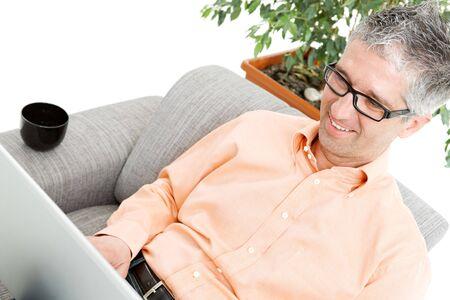 Happy man wearing orange shirt sitting on couch, browsing internet on laptop computer, smiling. photo