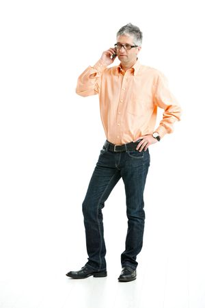 Grey haired man wearing jeans and orange shirt standing and talking on mobile phone. Isolated on white. photo
