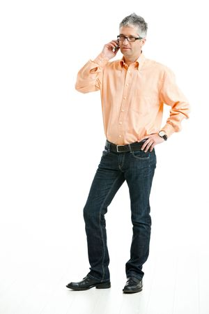 grey haired: Grey haired man wearing jeans and orange shirt standing and talking on mobile phone. Isolated on white.