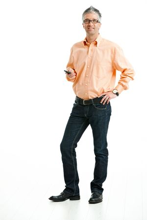 Mid-adult man wearing jeans and orange shirt standing and holding mobile phone. Isolated on white. photo