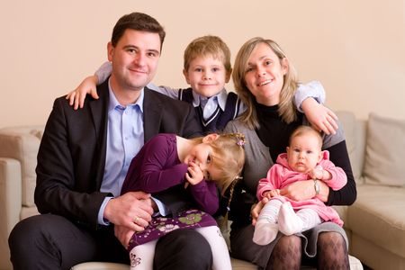 Portrait of happy family sitting on couch at home, smiling: father, mother, son, younger sister and a baby girl. Stock Photo - 5827843