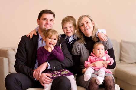 Portrait of happy family sitting on couch at home, smiling: father, mother, son, younger sister and a baby girl. photo