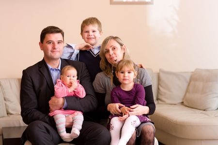 Portrait of happy family sitting on couch at home, smiling: father, mother, son, younger sister and a baby girl. Stock Photo - 5827833