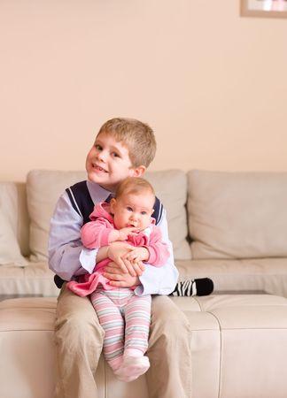 brat: 7 lat bratem gospodarstwa młodszą siostrę na kolanach, siedząc na kanapie z uśmiechem.