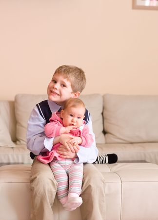 7 years old brother holding his little sister on his knees, sitting on couch, smiling.