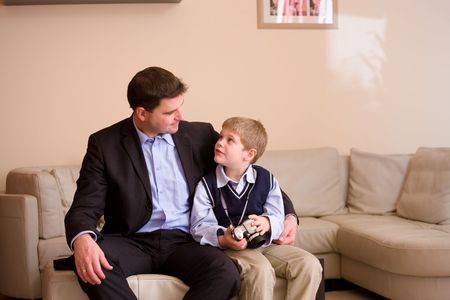 Father and son wearing a digital camera sitting together on couch at home, looking at each other. photo