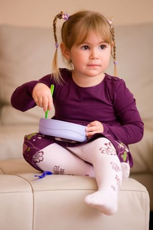purples: Little girl in purples dress, playing with plastic toy dishes, sitting on couch at home. Stock Photo