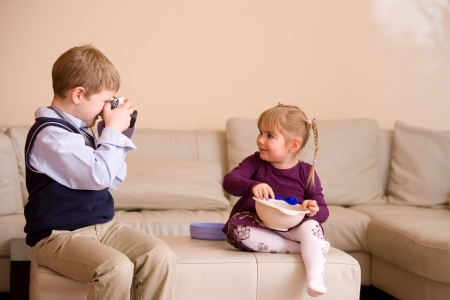 snug: Young boy sitting on couch, taking a picture of his happy little sister,