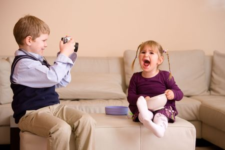 Young boy sitting on couch, taking a picture of his happy little sister, photo