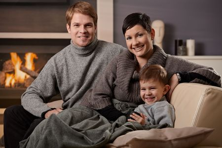 Happy family sitting on couch at home in front of fireplace, looking at camera, smiling.