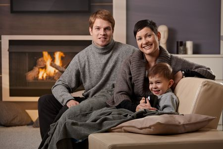 Happy family sitting on sofa at home in front of fireplace, looking at camera, smiling. photo