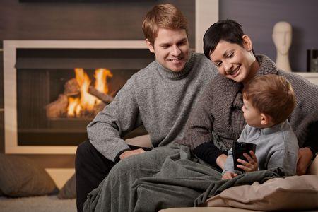 warm colors: De la familia feliz sentado en el sof� en casa delante de la chimenea, sonriendo. Foto de archivo