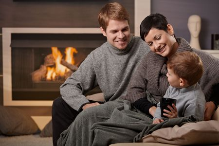 warm cloth: Happy family sitting on couch at home in front of fireplace, smiling.