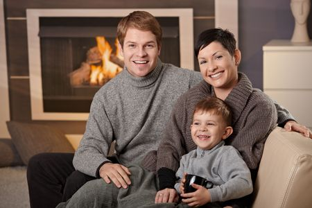 Happy family sitting on couch at home in front of fireplace, looking at camera, smiling. photo