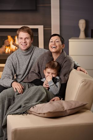 Happy family sitting on couch at home in front of fireplace, looking at camera, laughing. photo