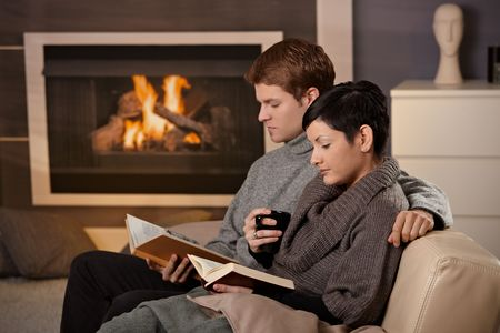 Young couple hugging on sofa in front of fireplace at home, reading books. Stock Photo - 5851145