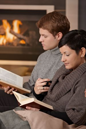 Young couple sitting on sofa in front of fireplace at home, reading books. photo
