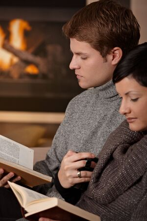 Young couple sitting in front of fireplace at home, reading books. photo