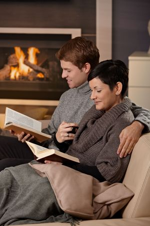 Young couple hugging on sofa in front of fireplace at home, reading books, smiling. photo