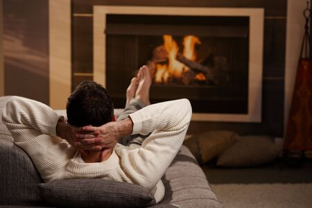 warm cloth: Man sitting on sofa at home in front of fireplace, rear view. Stock Photo