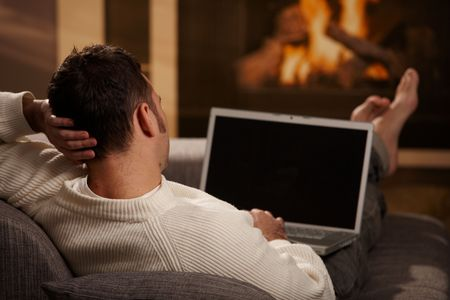laptop screen: Man sitting on sofa at home in front of fireplace and using laptop computer, rear view.
