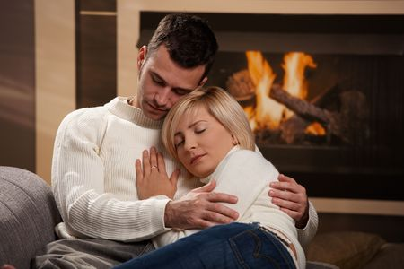 Young couple hugging on sofa in front of fireplace at home, eyes closed. photo