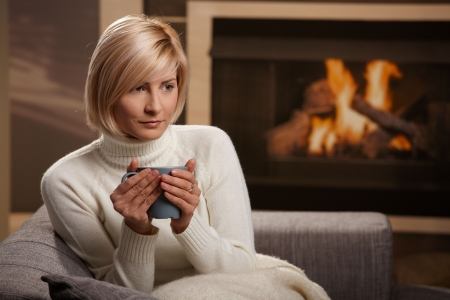 Woman sitting on sofa at home drinking hot tea, looking away. Stock Photo - 5851125