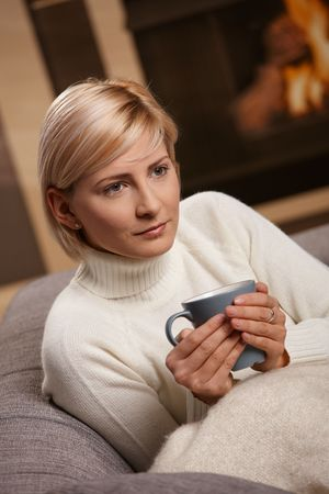 Woman sitting on sofa at home drinking hot tea, looking away. photo