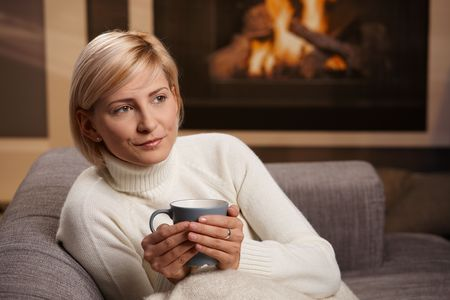 warm colors: Mujer sentada en el sof� en casa de beber t� caliente, apartando la mirada.